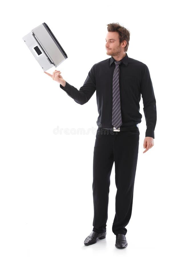 Homem novo que balança um portátil em seu forefinger foto de stock royalty free