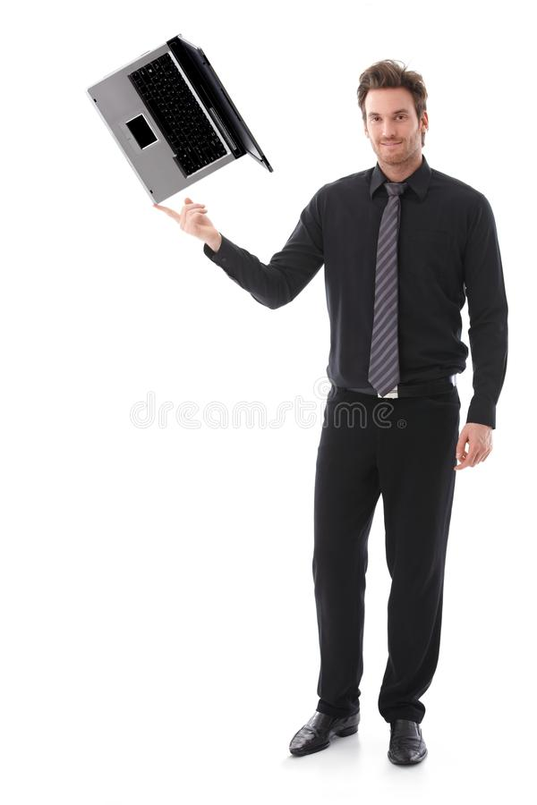 Homem novo que balança um portátil em seu forefinger imagem de stock royalty free