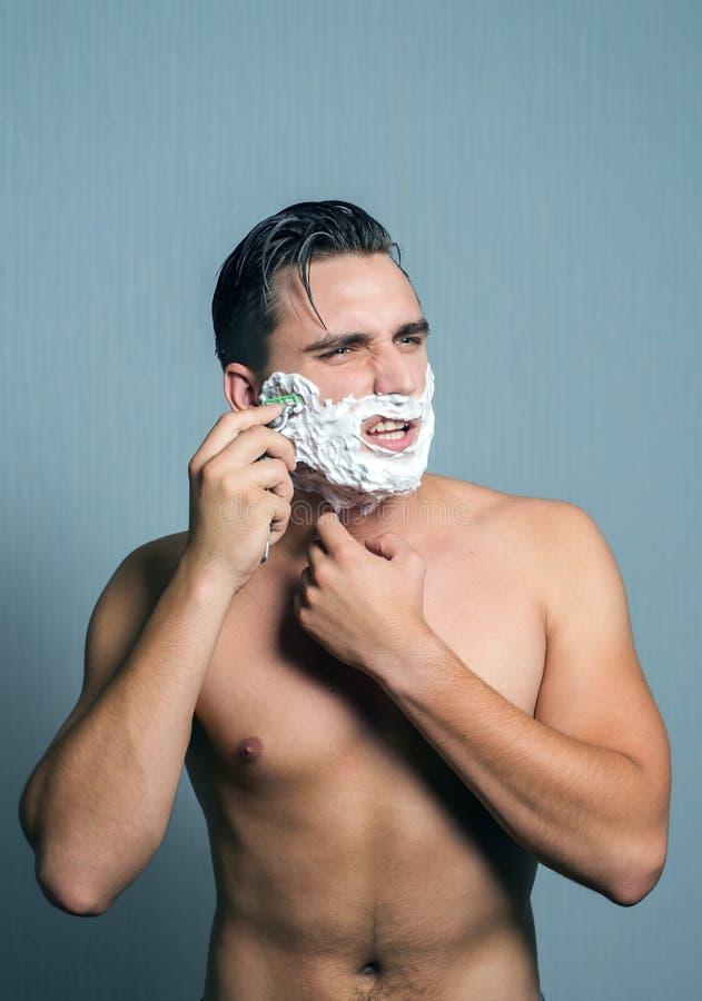 Homem novo que barbeia com ódio e agressão imagem de stock