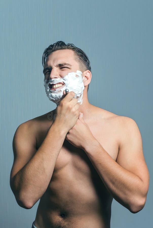 Homem novo que barbeia com ódio e agressão foto de stock royalty free