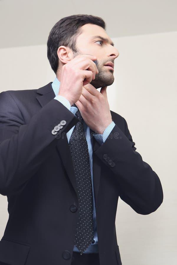 Homem novo que barbeia com lâmina elétrica foto de stock royalty free