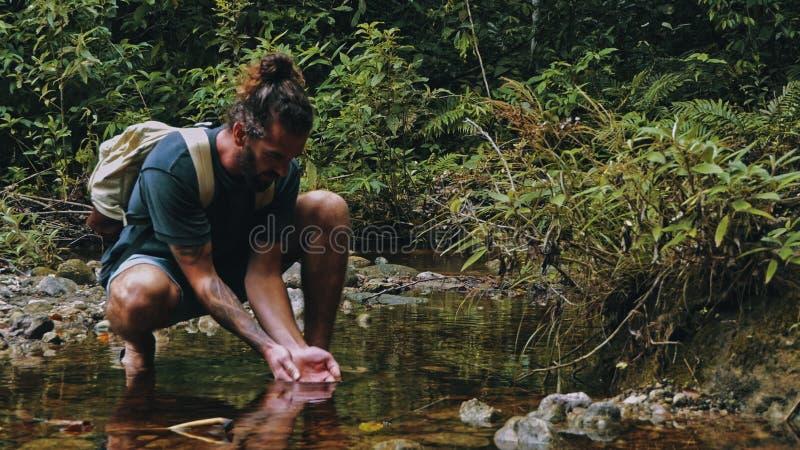 homem novo que bebe do rio claro no meio da floresta úmida tropical da selva foto de stock