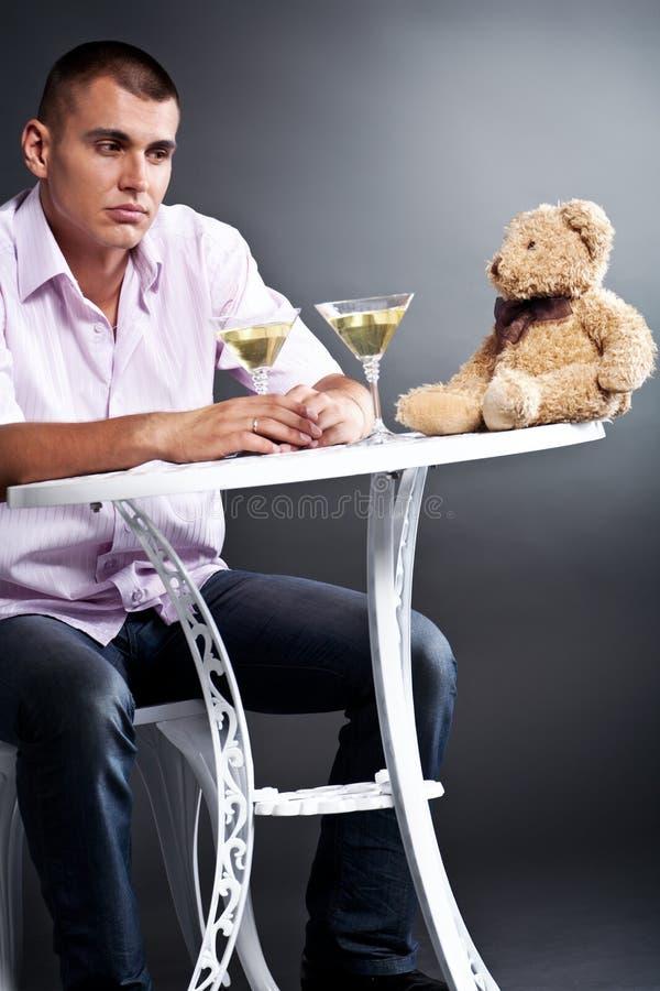 Homem novo que bebe martini com urso de peluche fotos de stock