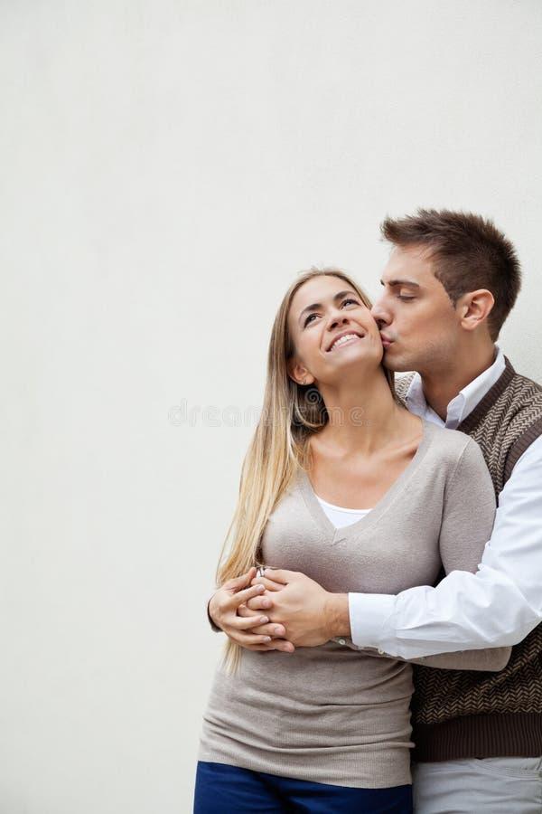 Homem novo que beija a amiga foto de stock royalty free