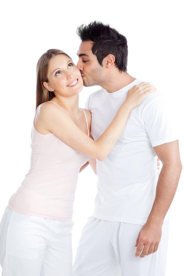 Homem novo que beija a jovem mulher foto de stock