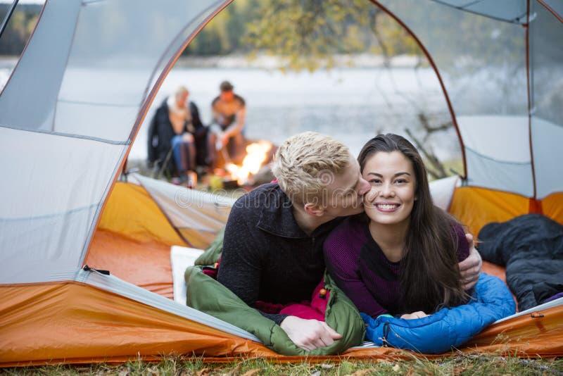 Homem novo que beija a mulher ao encontrar-se na barraca imagem de stock royalty free