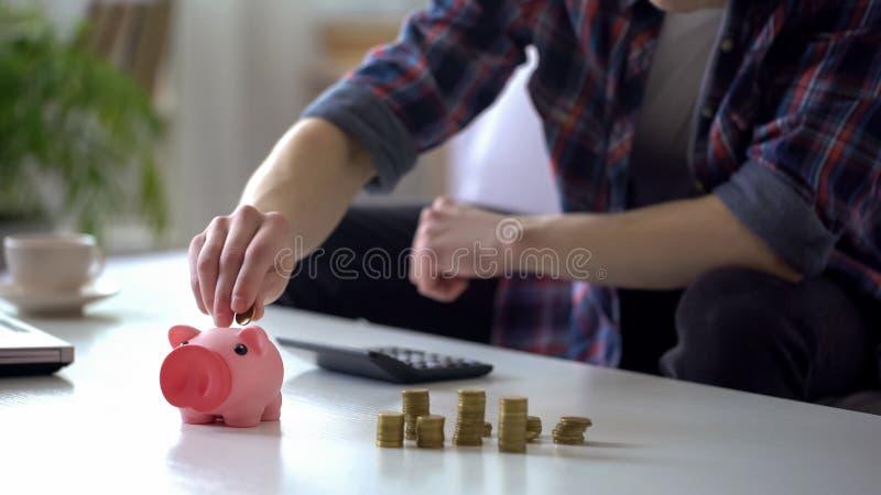 Homem novo que calcula o dinheiro, pondo moedas no mealheiro, orçamento de família foto de stock royalty free
