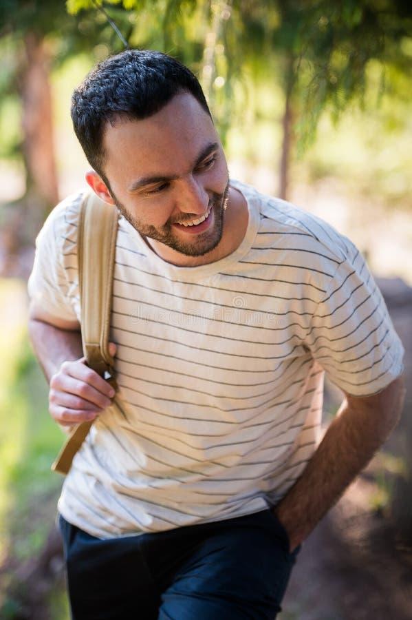 Homem novo que caminha o retrato feliz de sorriso Caminhante masculino que anda na floresta fotografia de stock royalty free