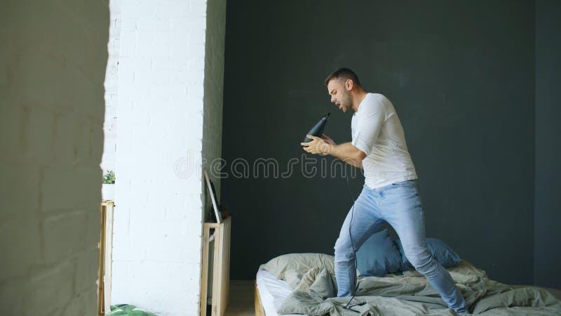 Homem novo que canta ao secador de cabelo e que dança na cama no quarto imagens de stock
