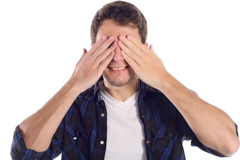 Homem novo que cobre seus olhos com as mãos fotografia de stock