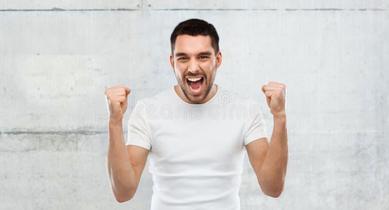Homem novo que comemora a vitória sobre o cinza fotografia de stock