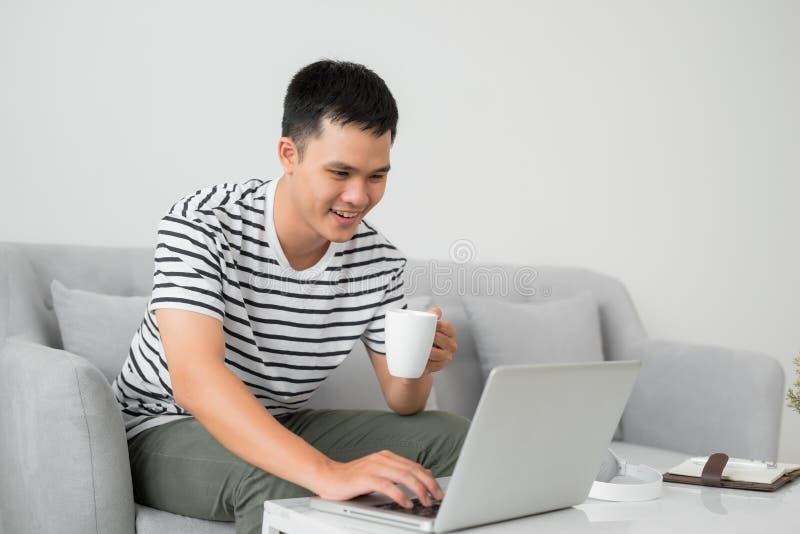 Homem novo que concentra-se na tela de laptop, sentando-se na mesa na sala de visitas, guardando a caneca fotografia de stock