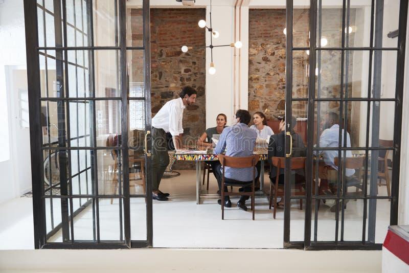 Homem novo que controla uma reunião da equipe em uma sala de reuniões foto de stock royalty free