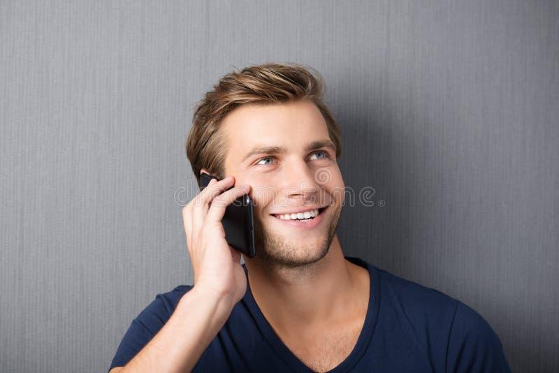 Homem novo que conversa em um smartphone imagem de stock
