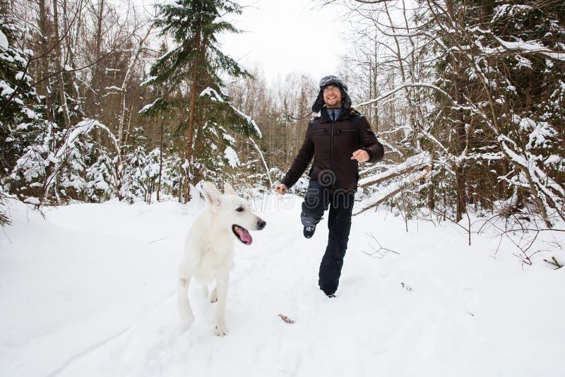 Homem novo que corre na floresta com cão branco foto de stock royalty free