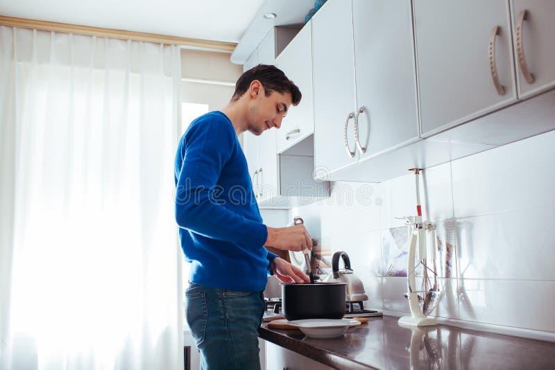 Homem novo que cozinha na cozinha em casa imagem de stock