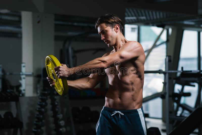 Homem novo que dá certo com pesos no gym foto de stock royalty free