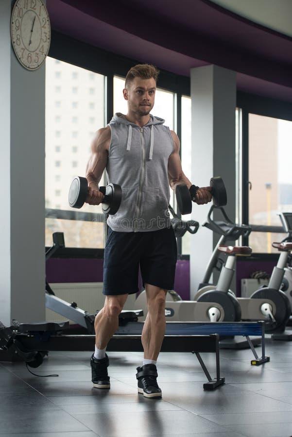 Homem novo que dá certo o bíceps fotografia de stock