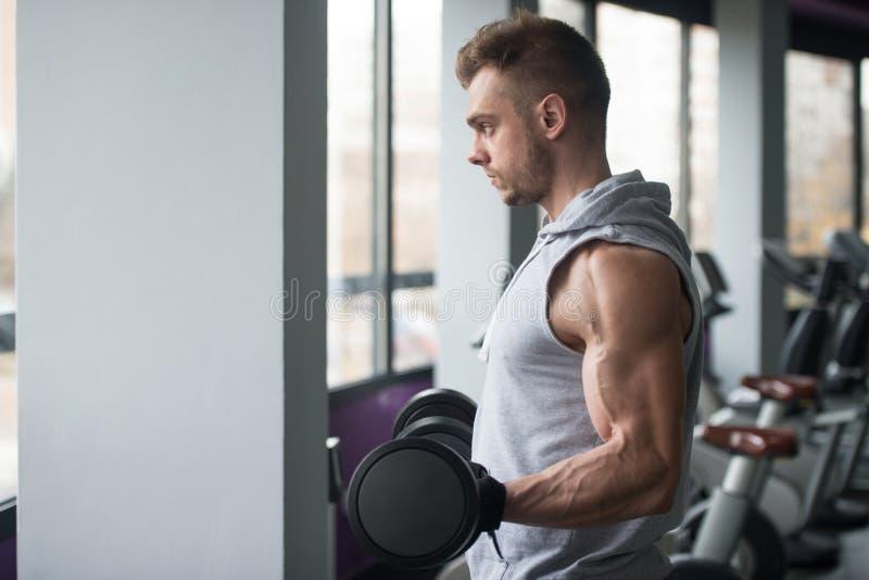 Homem novo que dá certo o bíceps fotografia de stock royalty free