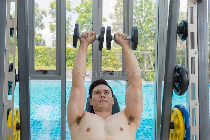 Homem novo que dá certo ombros com os pesos, treinando no gym imagens de stock royalty free