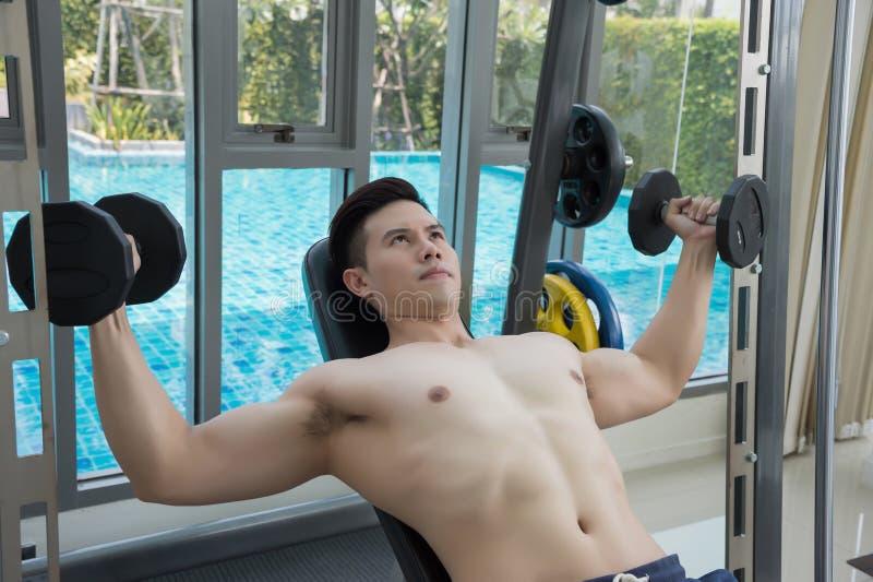 Homem novo que dá certo ombros com os pesos, treinando no gym imagem de stock royalty free