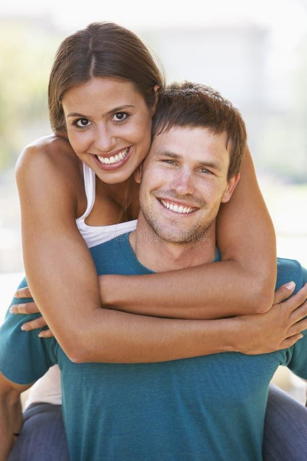 Homem novo que dá o sobreposto da mulher ao ar livre imagens de stock royalty free