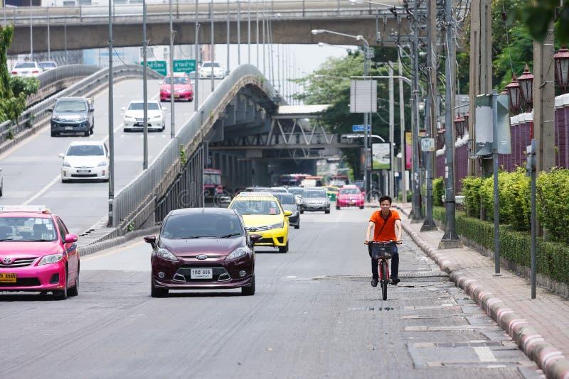 Homem novo que dá um ciclo uma bicicleta na rua fotografia de stock royalty free