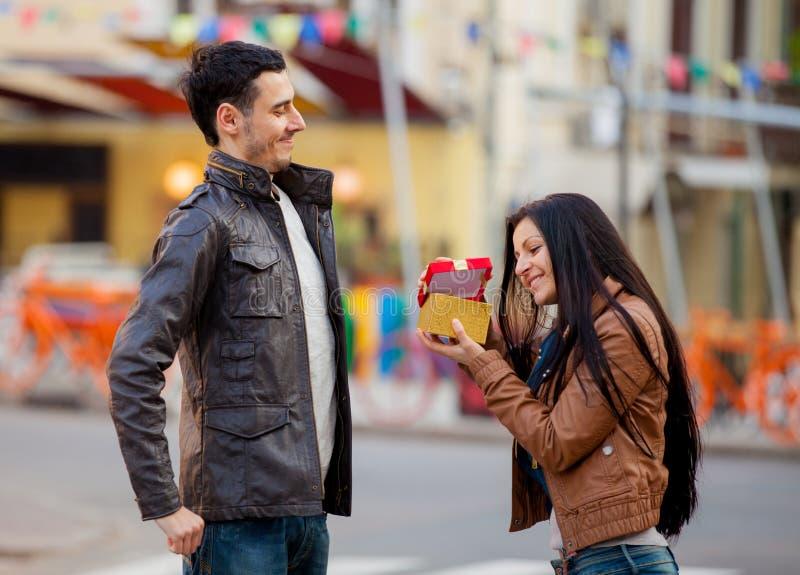 Homem novo que dá um presente a respeito de uma moça fotos de stock royalty free