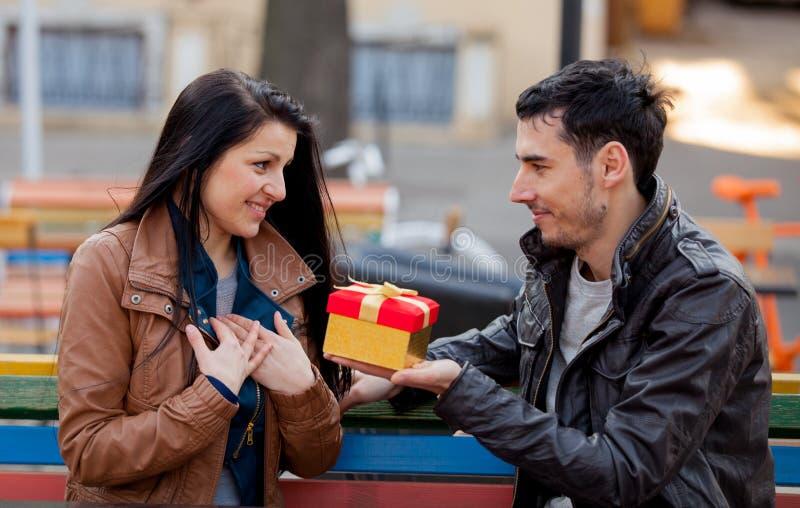 Homem novo que dá um presente a respeito de uma moça imagens de stock royalty free
