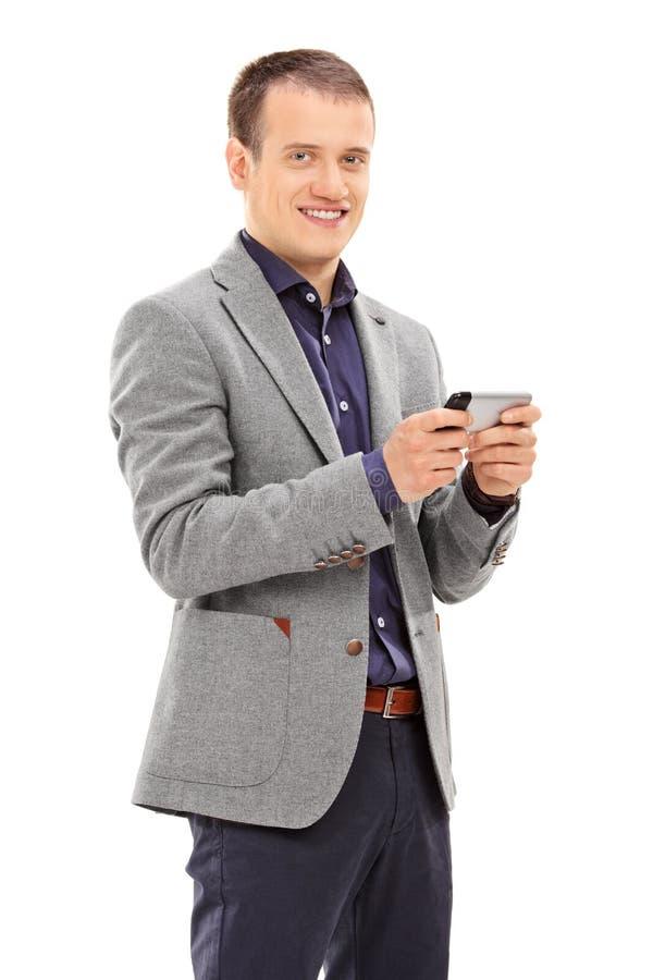 Homem novo que datilografa uma mensagem em seu telefone celular fotos de stock