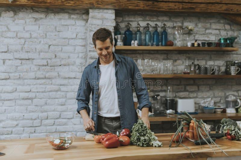 Homem novo que desbasta vegetais na cozinha e que prepara a refeição saudável imagens de stock royalty free