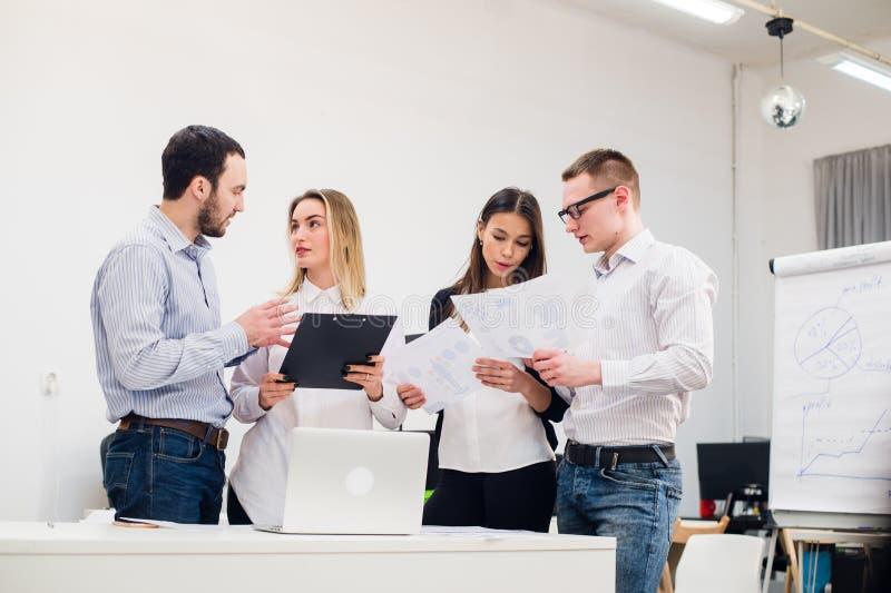Homem novo que discute estudos de mercado com os colegas em uma reunião Equipe dos profissionais que têm a conversação em imagem de stock