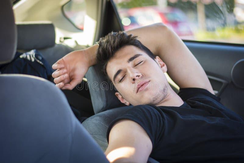 Homem novo que dorme dentro de seu carro, esgotado imagens de stock