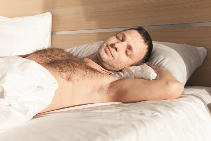 Homem novo que dorme na cama larga imagem de stock royalty free