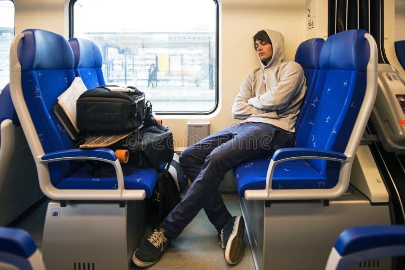 Homem novo que dorme no trem fotos de stock