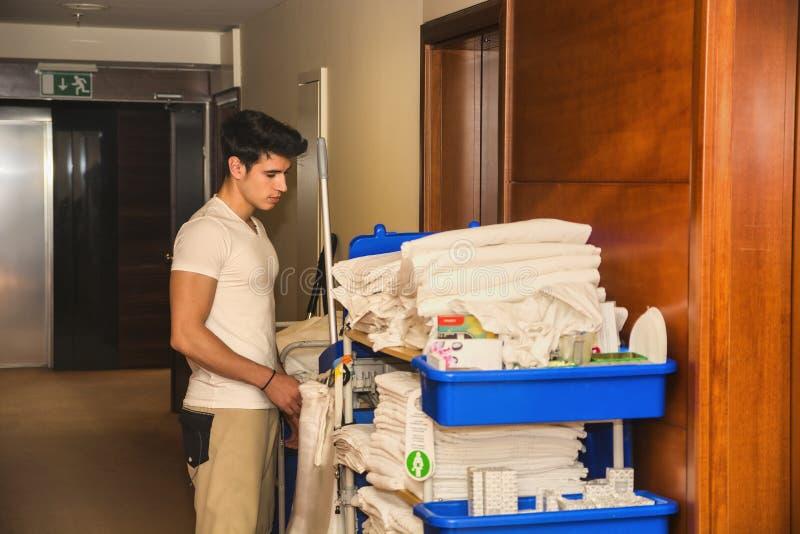 Homem novo que empurra um carro das tarefas domésticas em um hotel foto de stock