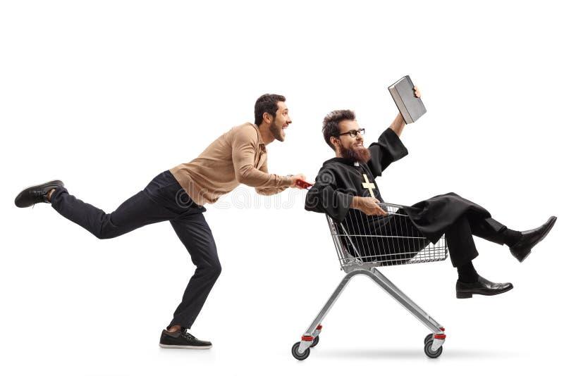 Homem novo que empurra um padre em um carrinho de compras fotos de stock royalty free
