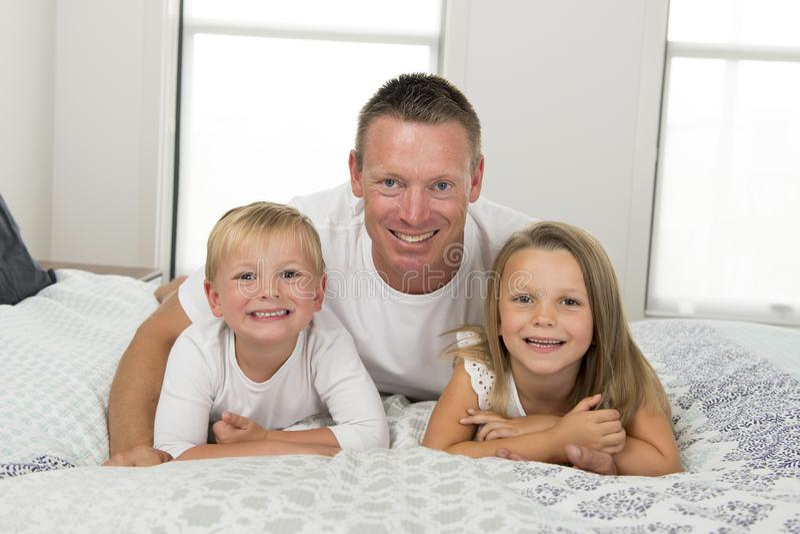 Homem novo que encontra-se na cama junto com seus jogo velho anos pequenos do filho do doce 3 e 7 e da filha feliz nas crianças l imagem de stock