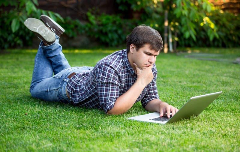 Homem novo que encontra-se na grama no parque e que usa o portátil fotografia de stock