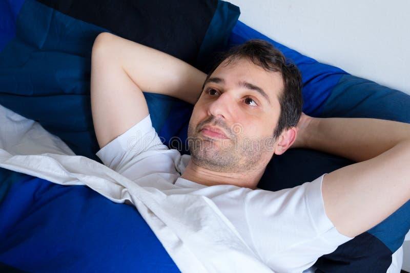 Homem novo que encontra-se no sentimento da cama mau e que tenta dormir no th fotos de stock