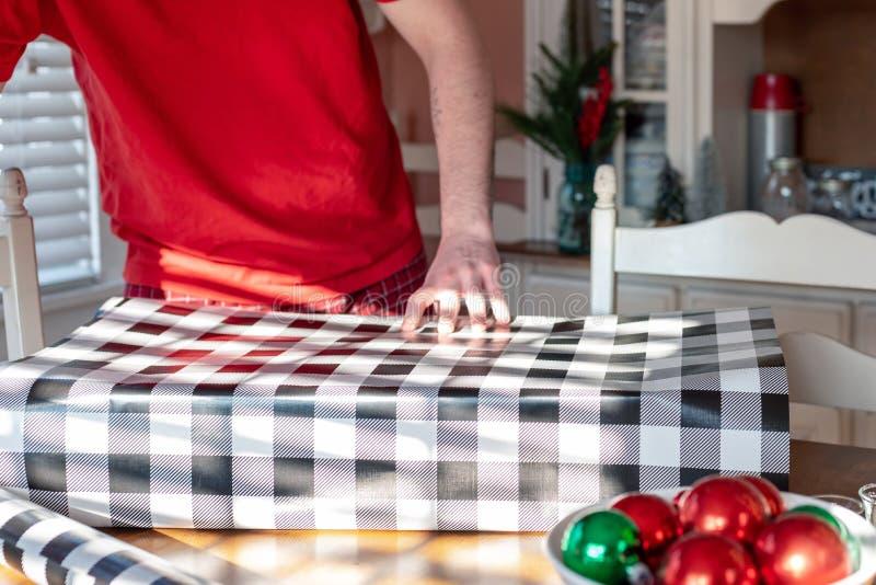 Homem novo que envolve presentes de Natal foto de stock royalty free