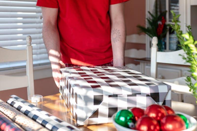 Homem novo que envolve presentes de Natal fotos de stock royalty free