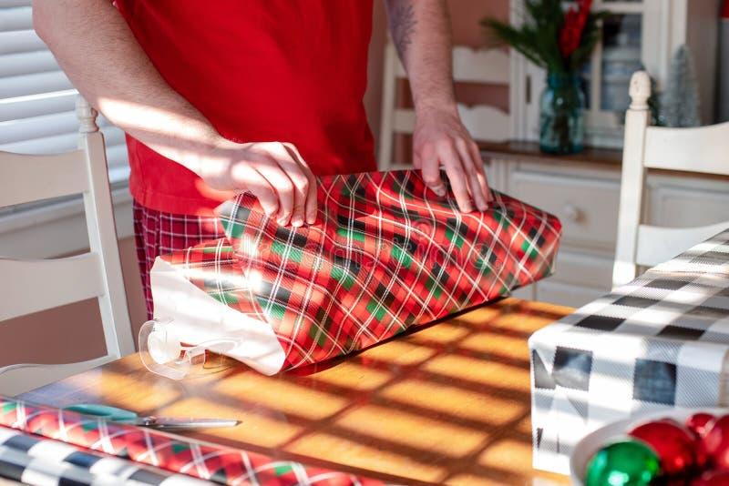 Homem novo que envolve presentes do Natal imagem de stock