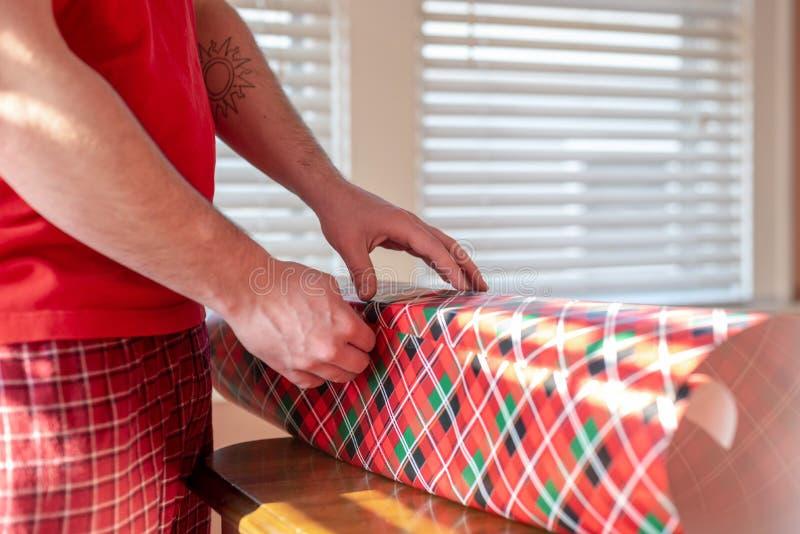 Homem novo que envolve presentes do Natal, mãos somente foto de stock