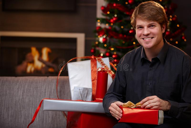 Homem novo que envolve presentes no Natal imagem de stock royalty free