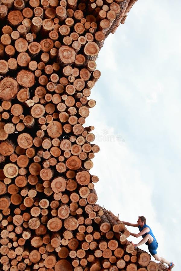 Homem novo que escala a grande pilha do lo de madeira do corte foto de stock royalty free