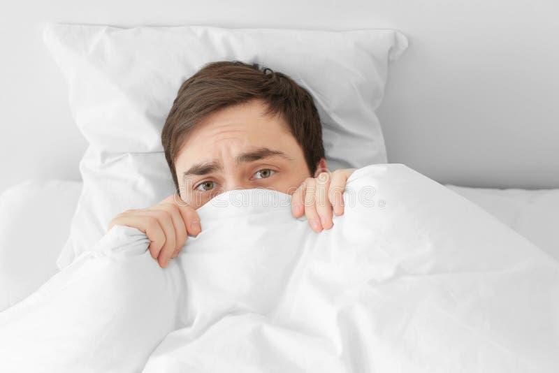 Homem novo que esconde sob a cobertura ao encontrar-se na cama imagens de stock