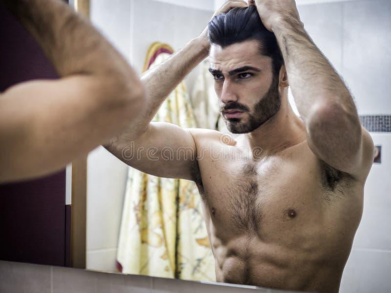 Homem novo que escova e que penteia o cabelo no espelho fotografia de stock