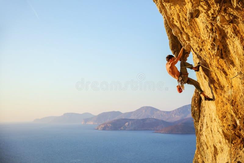 Homem novo que esforça-se para escalar a rota desafiante no penhasco foto de stock