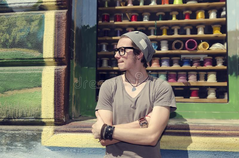 Homem novo que espera em uma rua na frente da loja da fita com antecipação Morda seus bordos fotos de stock